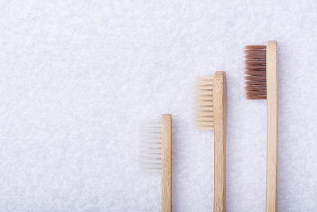En haut au-dessus de la vue aérienne photo de trois brosses à dents écologiques en bambou isolées sur fond de serviette blanche