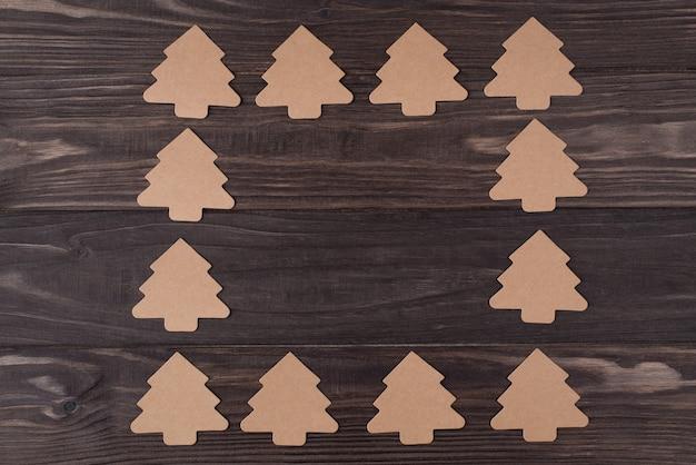 Haut au-dessus de la vue aérienne à plat photo de décorations en papier en forme d'arbre de noël faisant un carré isolé sur fond de bois avec fond