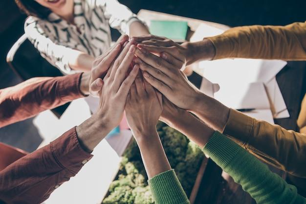 Haut au-dessus de la vue en grand angle, les professionnels recadrés, les entrepreneurs, les partenaires ont un coaching de consolidation d'équipe en ressources humaines mis les mains en haut