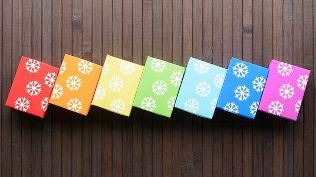 D'en haut des cadeaux colorés de noël dans une rangée sur une table en bois.