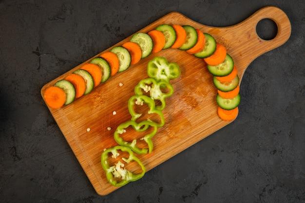 Haut de carottes et de concombre et de poivrons en tranches sur une planche à découper en bois sur fond noir