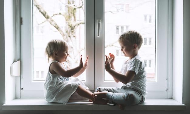 Haut cinq petits enfants sur fond de fenêtre symbole de sécurité de garde d'enfants vie de famille