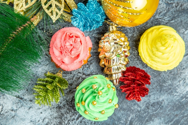 Haut fermer la vue des cupcakes colorés ornements de noël sur fond gris
