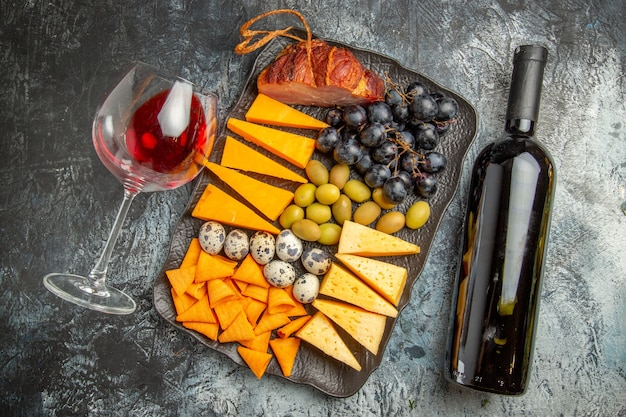 Haut de la meilleure collation savoureuse sur un plateau marron et verre de vin et bouteille tombés sur fond de glace