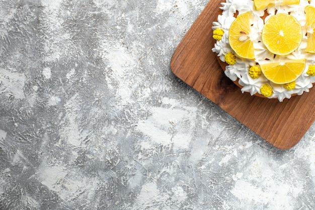 Haut de la moitié du gâteau avec de la crème blanche et des tranches de citron sur une planche à découper