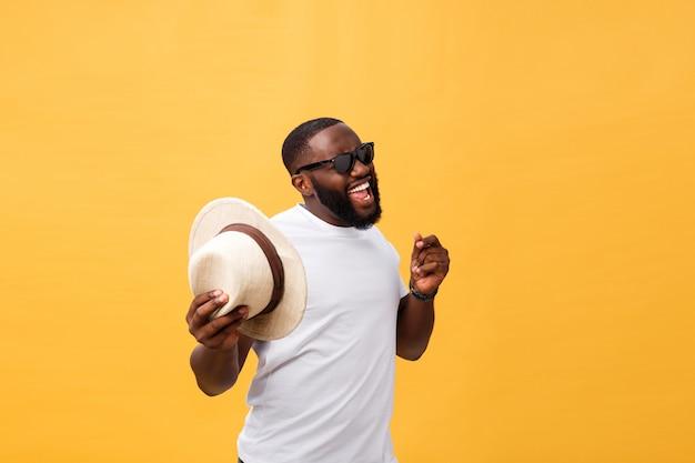 Haut noir jeune homme dansant isolé sur fond jaune.