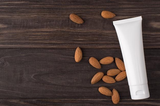 Haut de la page au-dessus de la vue à plat voir photo d'un récipient en plastique blanc pour la crème aux amandes isolées sur fond de bois brun avec un espace vide