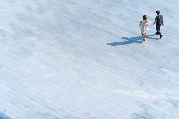 Haut de la page vue aérienne quelques personnes marchent sur du béton pour piétons avec une ombre noire sur le sol