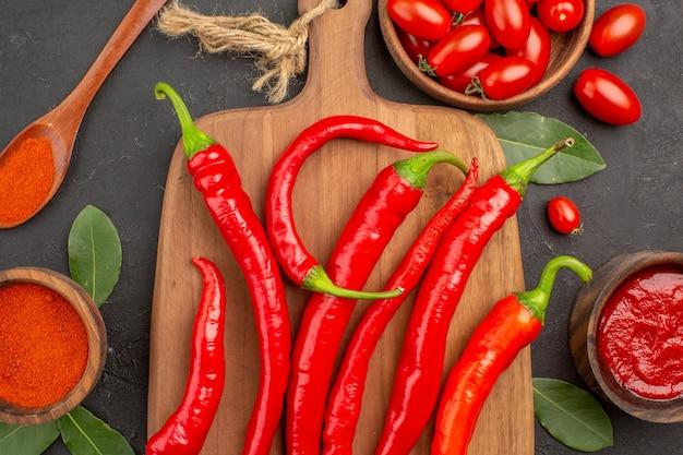 Haut de la page vue rapprochée d'un bol de tomates cerises piments rouges chauds sur la planche à découper
