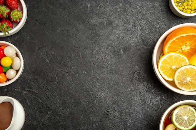 Haut de la page vue rapprochée des bonbons et des baies la tasse de thé au citron et les bols d'herbes au chocolat, d'agrumes et de baies