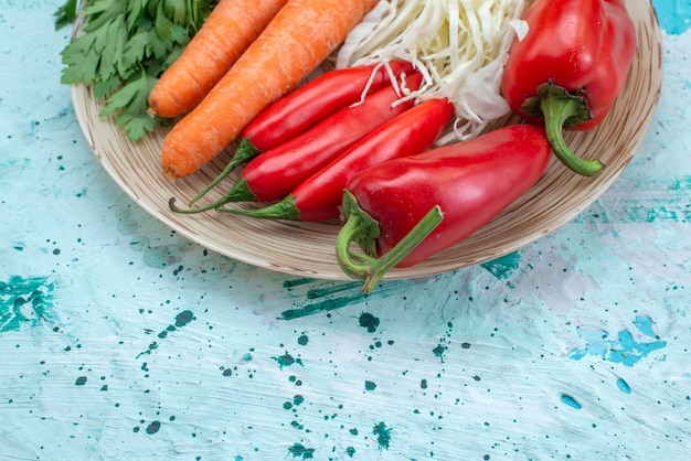 Haut de la page vue rapprochée de composition végétale chou carottes verts et poivrons rouges épicés sur bureau bleu vif