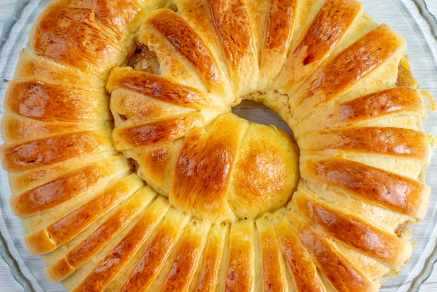 Haut de la page vue rapprochée cuit au four délicieux bracelet de pâtisserie formé à l'intérieur de la plaque sur blanc, biscuit pâtisserie sucre sucré