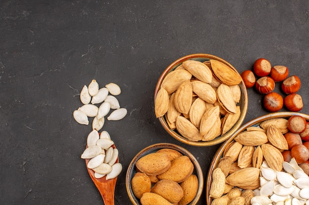 Haut de la page vue rapprochée de différentes noix noix fraîches à l'intérieur de pots sur une surface sombre
