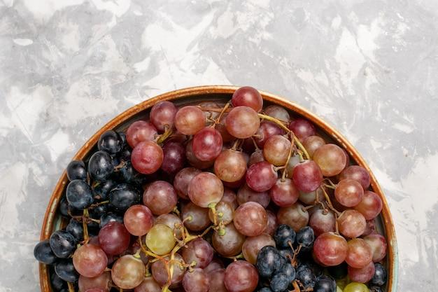 Haut de la page vue rapprochée de différents raisins juteux fruits aigres moelleux sur un bureau blanc léger fruits frais de jus de vin