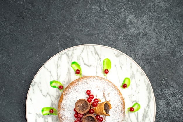 Haut de la page vue rapprochée d'un gâteau plaque grise d'un gâteau avec sauce verte baies de sucre en poudre