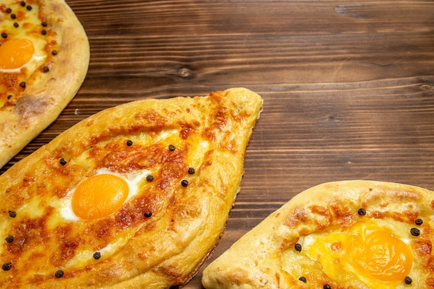 Haut de la page vue rapprochée des pains aux œufs au four fraîchement sortis du four sur la pâte de bureau en bois brun petit-déjeuner pain aux œufs