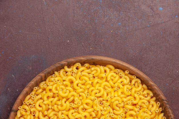 Haut de la page vue rapprochée des pâtes italiennes crues peu formées sur un espace sombre