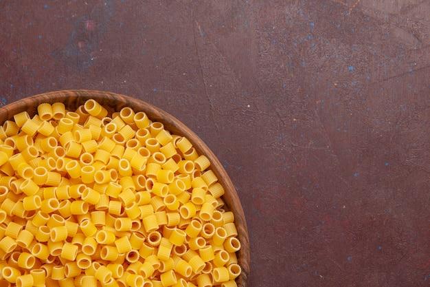 Haut de la page vue rapprochée de pâtes italiennes jaunes crues peu formées sur un espace sombre