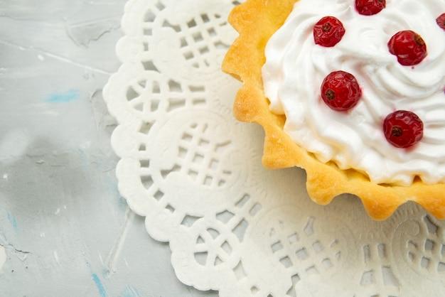 Haut de la page vue rapprochée petit délicieux gâteau à la crème et aux canneberges rouges isolés sur la surface claire