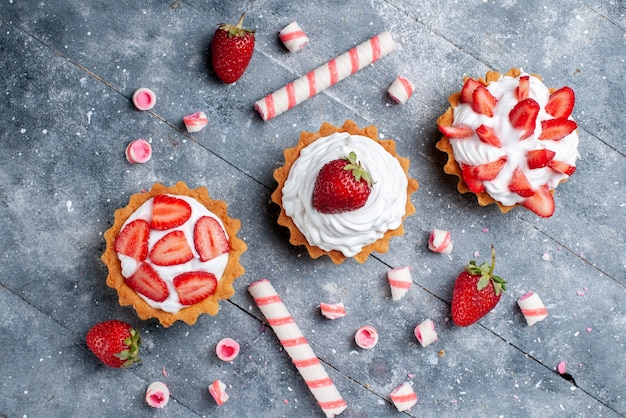 Haut de la page vue rapprochée de petits gâteaux crémeux avec des fraises fraîches et tranchées avec des bonbons bâton sur un bureau gris