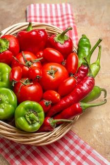 Haut de la page vue rapprochée poivrons verts et rouges piments forts tomates dans un panier en osier torchon sur fond ambre