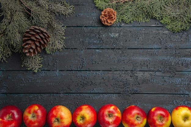 Haut de la page vue rapprochée rangée de pommes rangée de pommes sous les branches d'arbres avec des cônes