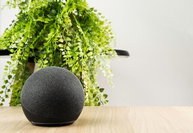 Haut-parleur intelligent et assistant virtuel. il est utilisé pour garder la maison connectée et donner des ordres par la voix à d'autres appareils électroniques. technologie moderne. fond en bois.