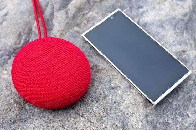 Haut-parleur portable sans fil rouge et smartphone allongé sur une pierre.