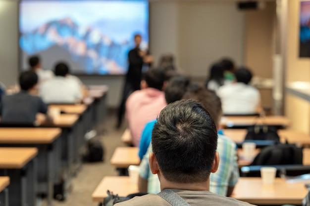 Haut-parleur sur la scène devant la salle avec vue arrière de l'audience dans la main levée