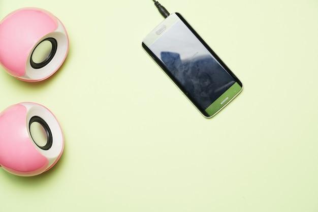 Haut-parleurs d'ordinateur et téléphone intelligent sur fond vert. mise à plat. conception plate