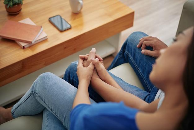 Haut plan d'une femme asiatique assise sur un canapé avec un homme, la tête sur son épaule et se tenant la main