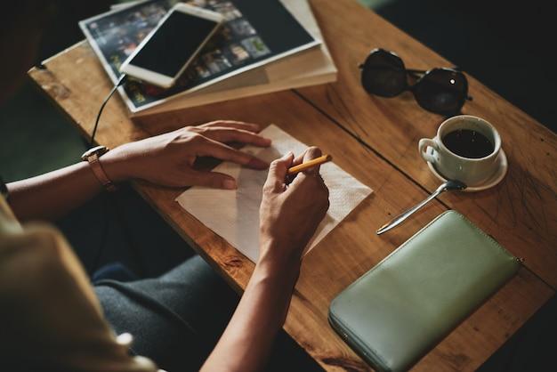 Haut plan de mains féminines dessinant sur une serviette au café