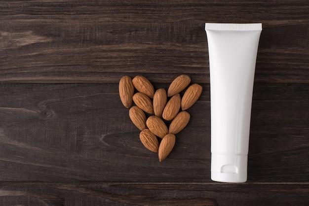 Haut plat au-dessus de la vue en gros plan photo d'une bouteille de crème en étiquette blanche avec des noix d'amandes isolées sur fond de bois de couleur marron