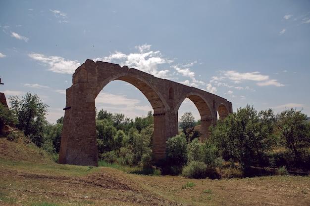 Haut pont de pierre en ruine se dresse en été dans un champ au-dessus de la rivière