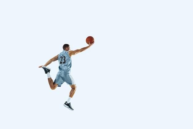 Haut vol. jeune joueur de basket-ball caucasien de l'équipe en action, mouvement en saut isolé sur fond blanc. concept de sport, mouvement, énergie et mode de vie sain et dynamique. entraînement, pratique.