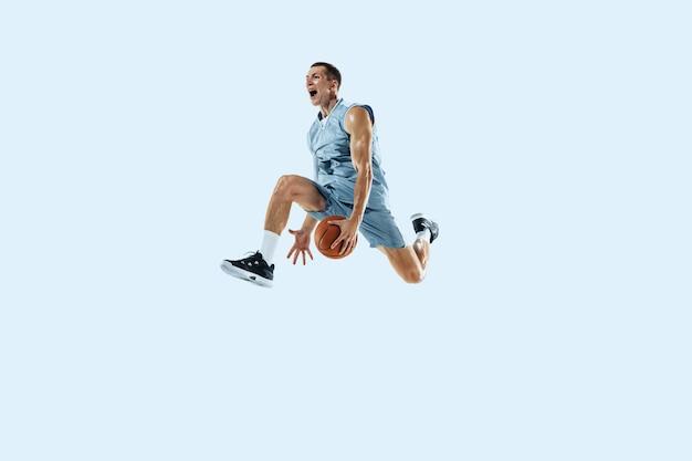 Haut vol. jeune joueur de basket-ball caucasien de l'équipe en action, mouvement en saut isolé sur fond bleu. concept de sport, mouvement, énergie et mode de vie sain et dynamique. entraînement, pratique.