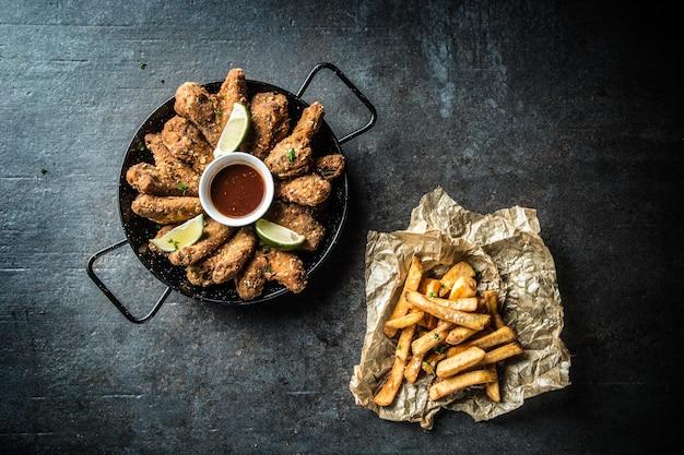 Haut de la vue ailes de poulet frit sauce chili citron vert et frites de pommes de terre.