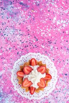 Haut de la vue éloignée du petit gâteau crémeux avec des fraises en tranches sur la lumière lumineuse, gâteau biscuit berry sweet bake