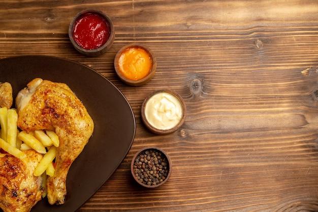 Haut vue en gros plan sauces colorées bols de sauces colorées et poivre noir à côté de l'assiette de poulet et frites