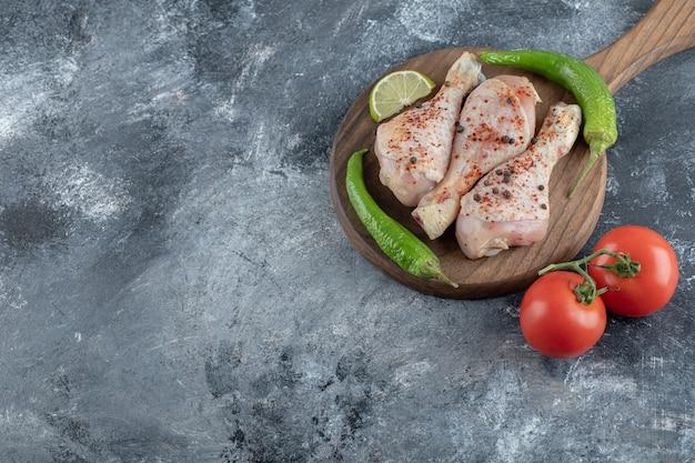 Haut. vue. pilons de poulet crus épicés au poivron vert et tomates.
