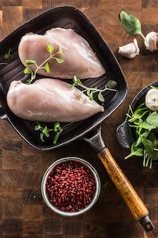 Haut de la vue poitrine de poulet crue dans une poêle à griller avec des herbes et des épices.