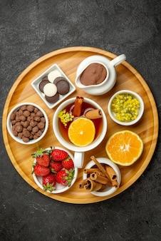Haut vue rapprochée des bonbons sur une assiette de table de fraises au chocolat, de bâtons de cannelle au citron et d'une tasse de thé au citron