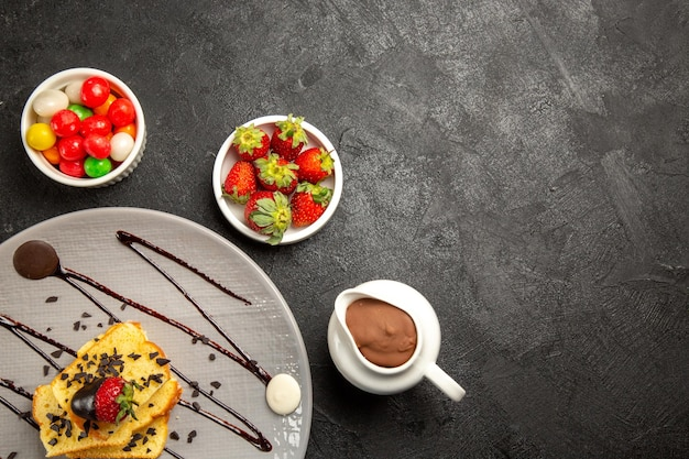 Haut vue rapprochée des bonbons bols de bonbons à côté d'une assiette grise de morceaux de gâteau avec sauce au chocolat et fraises