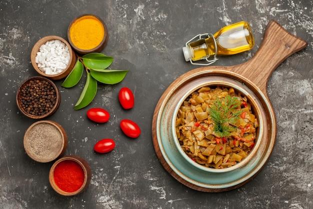 Haut vue rapprochée épices et plat haricots verts et tomates sur la planche à découper cinq épices feuilles tomates et bouteille d'huile sur la table