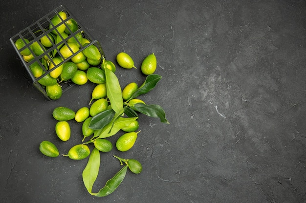Haut vue rapprochée des fruits agrumes avec des feuilles à côté du panier avec des fruits sur la table