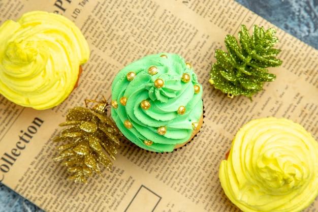 Haut vue rapprochée mini cupcakes ornements de noël sur papier journal sur fond sombre