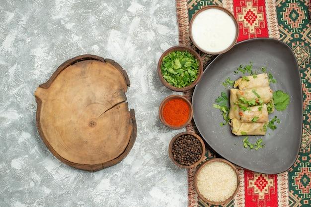 Haut vue rapprochée plat avec assiette d'herbes de chou farci et bols d'herbes épices papper noir