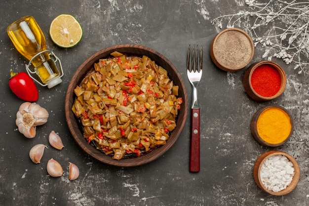 Haut vue rapprochée plat et épices fourchette assiette de haricots verts ail tomates poivrons quatre bols d'épices et bouteille d'huile