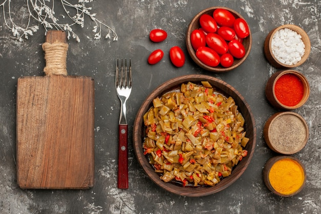 Haut vue rapprochée plat et épices planche à découper en bois assiette de fourchette de haricots verts et épices colorées sur le tableau noir