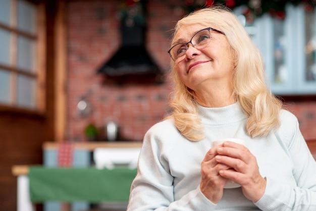 Haute angle femme âgée buvant du thé